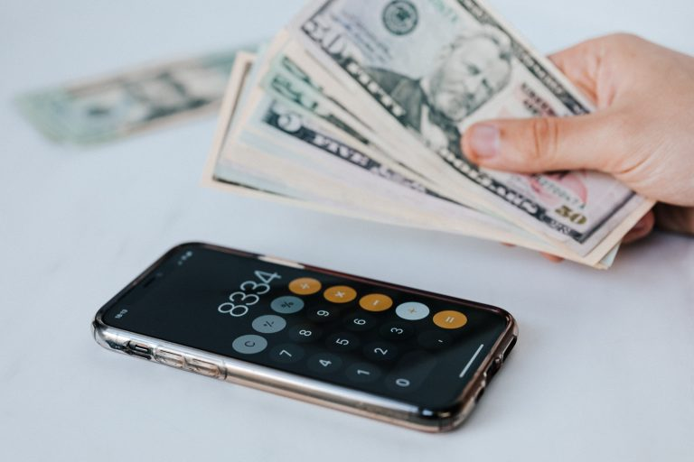 Debt Shown with a calculator and cash in hand